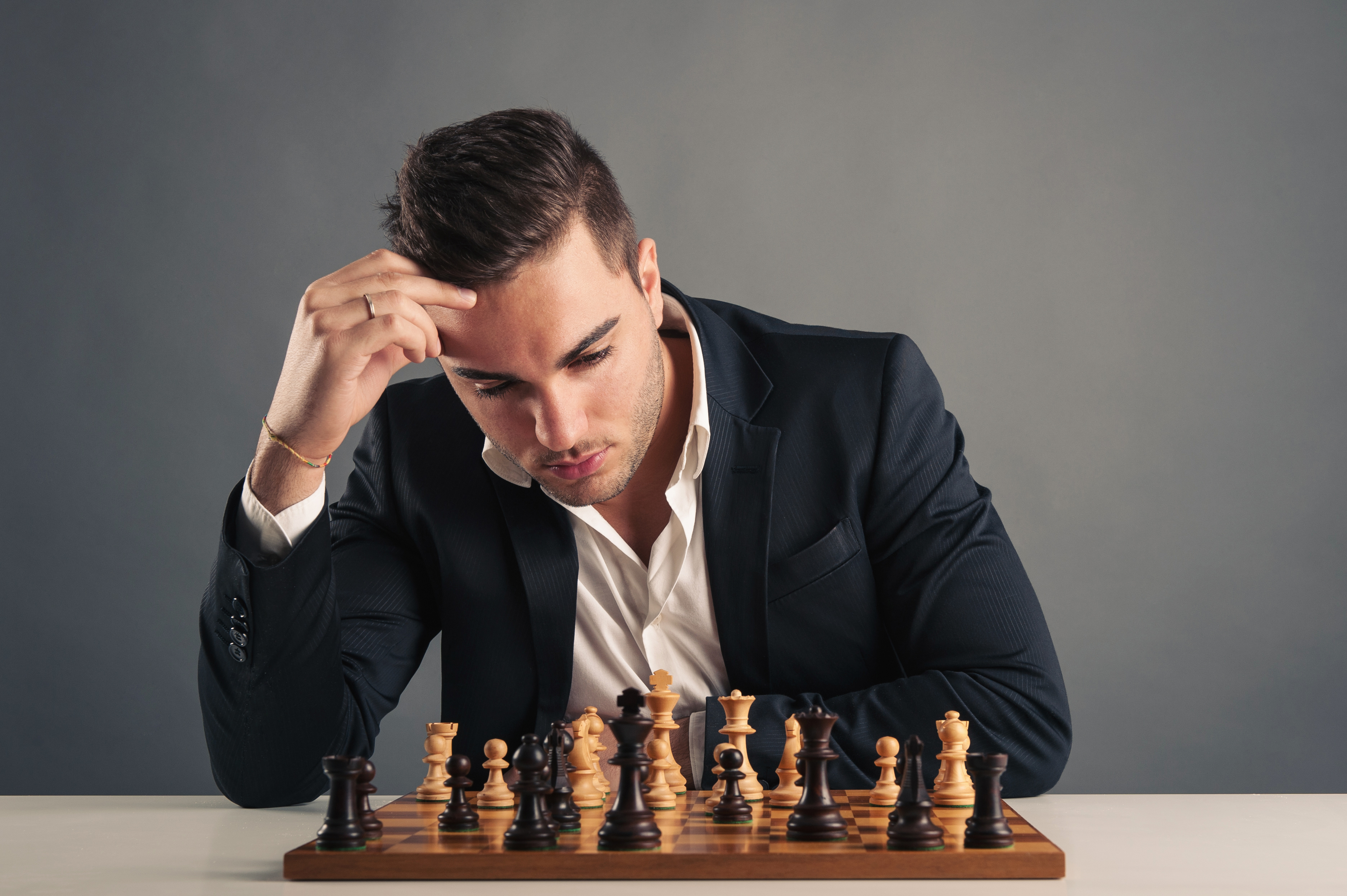 Man playing chess, isolated on dark background.